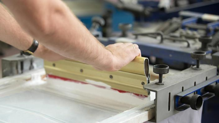 Close up of male hands exploring traditional squeegee, creating an image on white fabric clothing by pressing ink through a screen with areas blocked off by a stencil.
