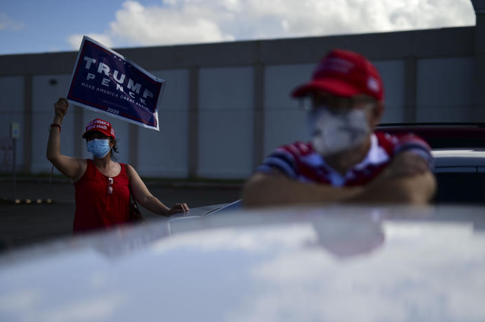 Supporters of President Donald Trump gather moments before leaving for the headquarters of the Republican party in support of his candidacy a few weeks before the presidential election next November, in Carolina, Puerto Rico, Sunday, Oct. 18, 2020. President Donald Trump and former Vice President Joe Biden are targeting Puerto Rico in a way never seen before to gather the attention of tens of thousands of potential voters in the battleground state of Florida. (AP Photo/Carlos Giusti)