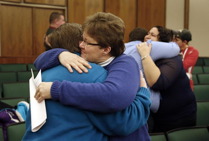 FILE - In this March 22, 2014 file photo Kat White, left, and Sue Walton hug after being married in a group ceremony by the Oakland County Clerk in Pontiac, Mich., after a federal judge has struck down Michigan's ban on gay marriage. Attorney General Eric Holder on Friday, March 28, 2014 extended federal recognition to the marriages of about 300 same-sex couples that took place in Michigan before a federal appeals court put those unions on hold. (AP Photo/Paul Sancya, File)