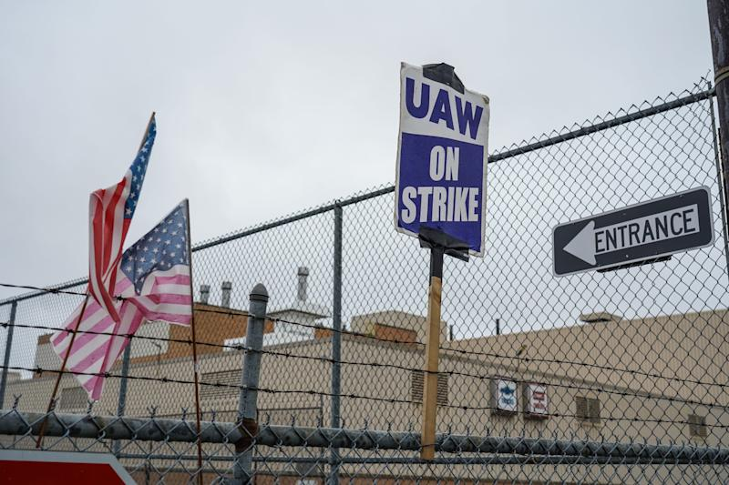 American flags and UAW strike signs sit attached to a fence outside of General Motors Flint Assembly as workers remain on strike with General Motors over contract negotiations on Wednesday, October 2, 2019.