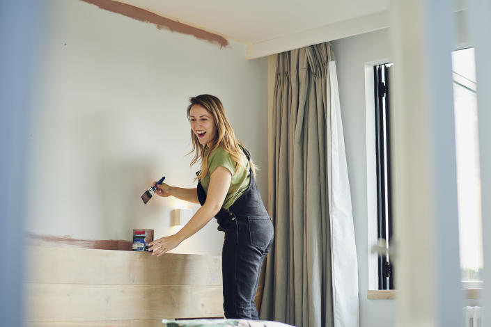 A young woman smiling while painting a wall