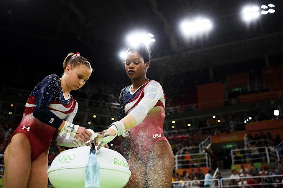 <p>Madison Kocian (L) and Gabrielle Douglas (R) of the United States apply chalk in preparation for competing on the uneven bars during the Artistic Gymnastics Women's Team Final on Day 4 of the Rio 2016 Olympic Games at the Rio Olympic Arena on August 9, 2016 in Rio de Janeiro, Brazil. (Photo by Laurence Griffiths/Getty Images) </p>