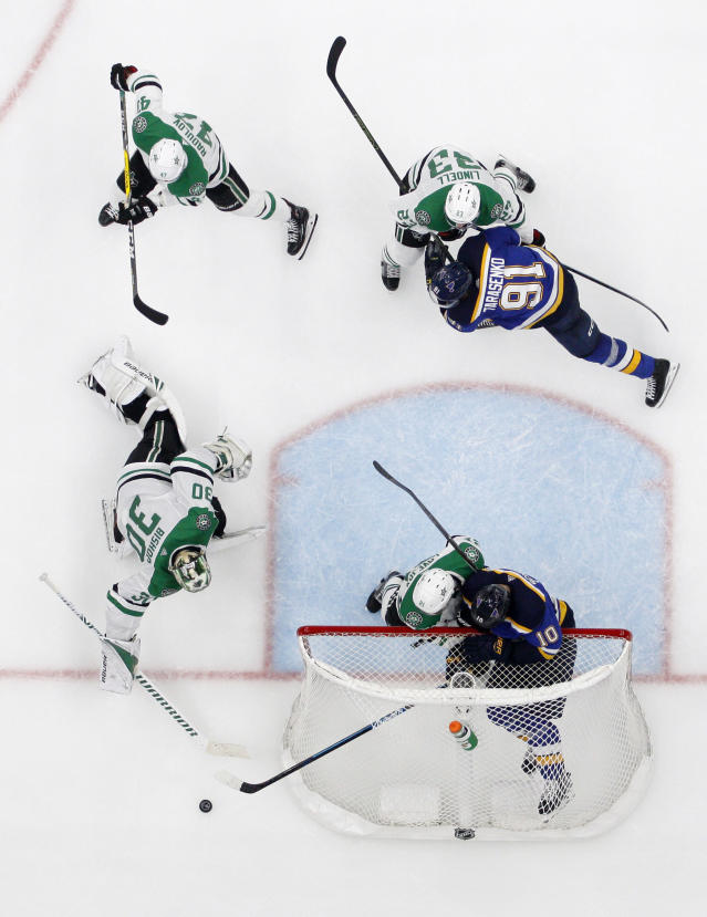 Dallas Stars goaltender Ben Bishop (30) reaches to clear a puck as Alexander Radulov (47), Esa Lindell (23) and Ben Lovejoy, left in net, help against pressure by St. Louis Blues right wing Vladimir Tarasenko (91) and center Brayden Schenn (10) during the third period in Game 7 of an NHL second-round hockey playoff series, Tuesday, May 7, 2019, in St. Louis. (AP Photo/Jeff Roberson)