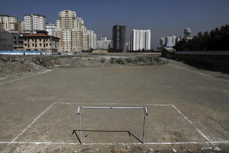 In this Thursday, March 12, 2020 photo, a empty soccer football field with dirt surface is seen in Tehran, Iran. The typically frenetic streets of Iran's capital, Tehran, have fallen silent and empty due to the new coronavirus outbreak that's gripped the Islamic Republic. The typically frenetic streets of Iran's capital, Tehran, have fallen silent and empty due to the new coronavirus outbreak that's gripped the Islamic Republic. (AP Photo/Ebrahim Noroozi)