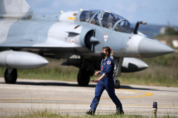 An air force officer walks as a Greek fighter jet Mirage 2000-5 taxis during the international military exercise Iniochos at Andravida air base, about 279 kilometres (174 miles) southwest of Athens, Tuesday, April 20, 2021. Greece vowed Tuesday to expand military cooperation with traditional NATO allies as well as Middle Eastern powers in a race to modernize its armed forces and face its militarily assertive neighbor Turkey. (AP Photo/Thanassis Stavrakis)