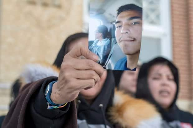 Debbie Baptiste, the mother of Colten Boushie, holds up a picture of her son during the 2018 trial of the man eventually acquitted in his shooting death. The accused's lawyer challenged every Indigenous jury candidate through peremptory challenges. (Liam Richards/The Canadian Press - image credit)