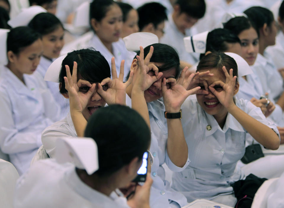 FILE PHOTO: Newly graduated nurses gesture while having their picture taken by a friend before the oath taking ceremony of the professional nurses inside a mall in Manila September 20, 2010. REUTERS/Romeo Ranoco