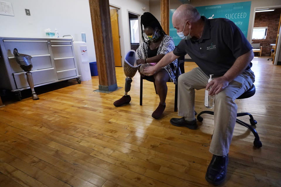 Arthur Graham, prosthetist at Next Step Bionics & Prosthetics, right, checks the fit of Claudine Humure's prosthetic leg, Monday, Sept. 20, 2021, in Newton, Mass. Humure, of Rwanda, was orphaned during her country's genocide and lost part of her leg to childhood cancer. Her new leg was provided free by the prosthetic clinic and features the latest in artificial limb technology. (AP Photo/Charles Krupa)
