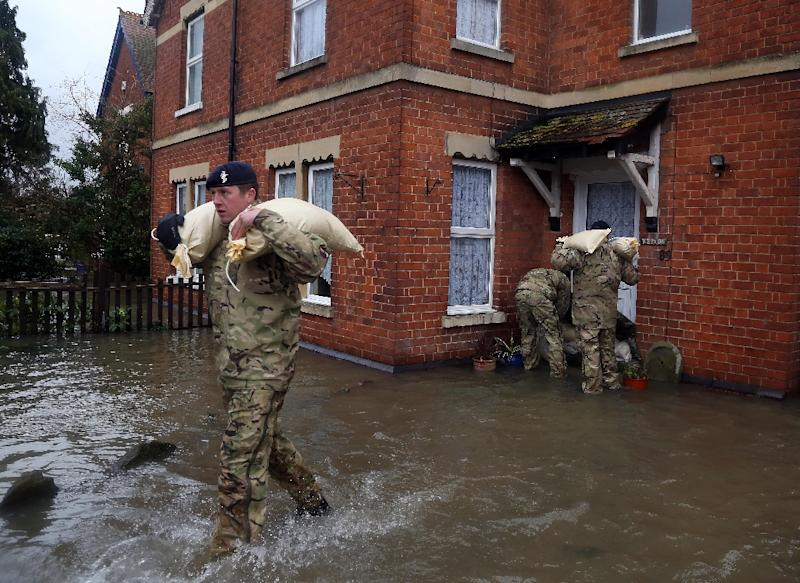 Soldiers deliver sand bags to residents whose houses are in danger of flooding, as the river Severn rises to record heights in Gloucester, western England, on February 14, 2014