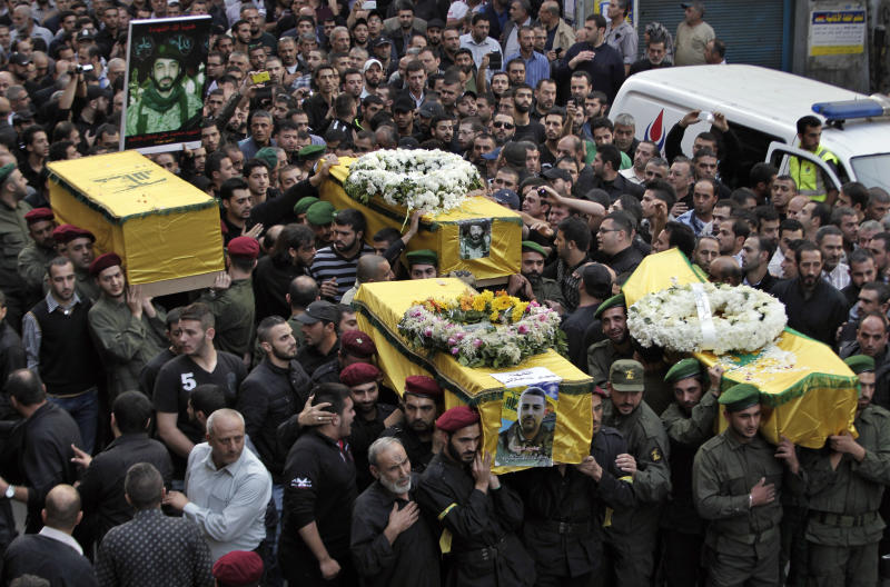 Hezbollah supporters carry the coffins of four people, including Radwan Fares, a Lebanese national who headed the facility's security, who were killed a day after two suicide bombings struck the Iranian Embassy in Beirut, during their funeral procession, in the southern suburb of Beirut, Lebanon, Wednesday, Nov. 20, 2013. Thousands of people attended the funerals in Ghobeiri, a stronghold of Hezbollah in southern Beirut. At least 23 people were killed and more than 140 were wounded in Tuesday's twin suicide attacks. (AP Photo/Bilal Hussein)