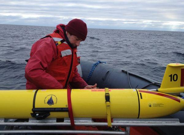 Woods Hole Oceanographic Institution scientist Mark Baumgartner secures a glider (with its wings removed) after it was recovered Dec. 4 from its three-week mission to record and transmit whale song.