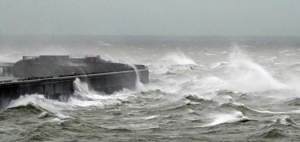 Waves crash over the harbour wall in Dover, Kent, during strong winds and rain, whilst a lone seagull braves the weather.