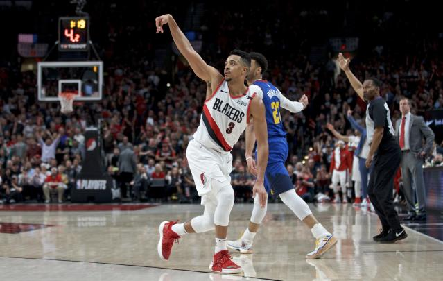 Portland Trail Blazers guard CJ McCollum, front, reacts after making a 3-point basket over Denver Nuggets guard Jamal Murray during the second half of Game 6 of an NBA basketball second-round playoff series Thursday, May 9, 2019, in Portland, Ore. The Trail Blazers won 119-108. (AP Photo/Craig Mitchelldyer)