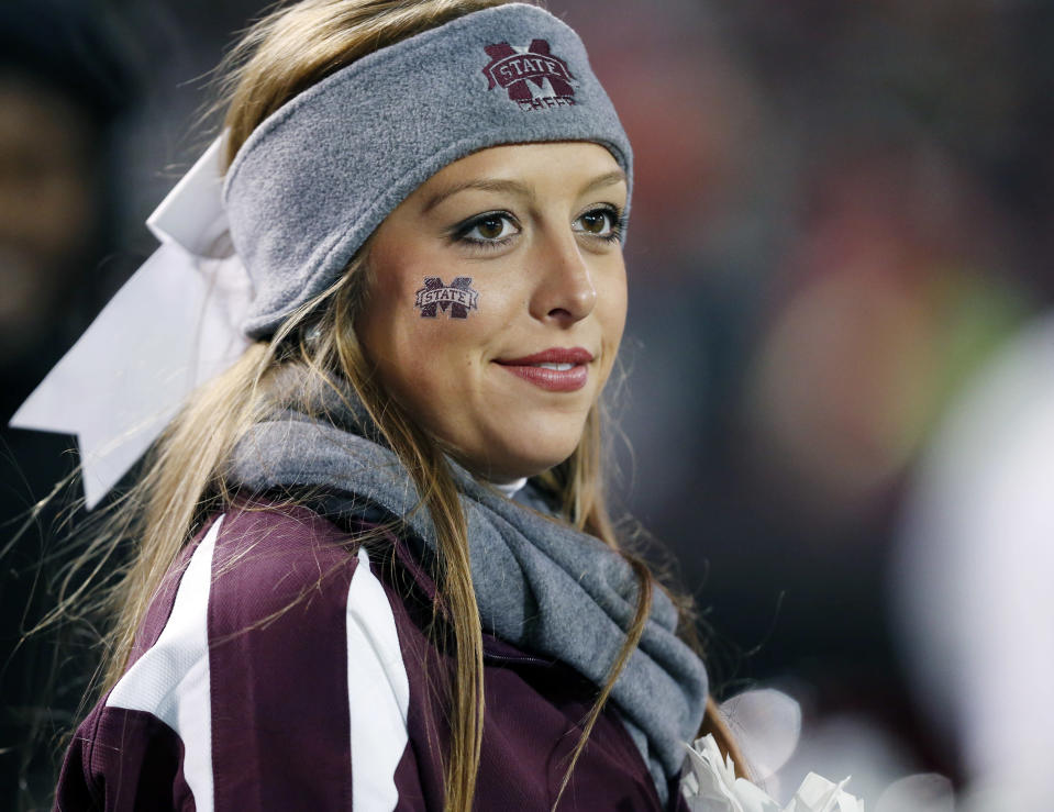 A Mississippi State cheerleader is bundled up for their NCAA college football game against Arkansas in Starkville, Miss., Saturday, Nov. 1, 2014. No. 1 Mississippi State won 17-10. (AP Photo/Rogelio V. Solis)