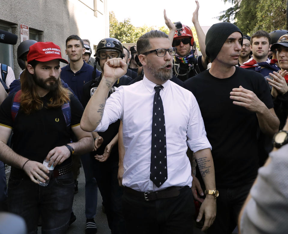 "FILE - In this April 27, 2017 file photo, Gavin McInnes, center, founder of the far-right group Proud Boys, is surrounded by supporters after speaking at a rally in Berkeley, Calif. The Canadian government designated the Proud Boys group as a terrorist entity on Wednesday, Feb. 3, 2021, noting they played a pivotal role in the insurrection at the U.S. Capitol on Jan. 6. McInnes has described the group as a politically incorrect men's club for ""Western chauvinists"" and denies affiliations with far-right extremist groups that overtly espouse racist and anti-Semitic views. (AP Photo/Marcio Jose Sanchez, File)"