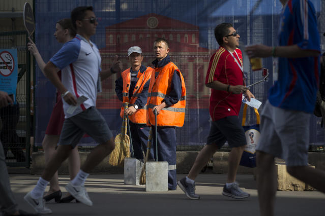 In this photo taken on Tuesday, June 26, 2018, Two municipal workers stand ready to clean an area ahead of the Denmark-France World Cup match at Moscow's Luzhniki Stadium in Moscow, Russia, Tuesday, June 26, 2018. Legions of migrant workers, most of them are from Central Asia and elsewhere are the unsung heroes of Russia's World Cup, endlessly cleaning stadium grounds and fan zones but unable to watch the world-class soccer unfolding in their midst. (AP Photo/Alexander Zemlianichenko)