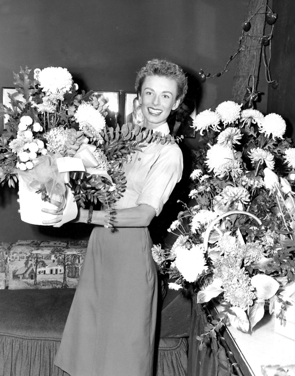 "FILE - Cloris Leachman is shown in her dressing room at the Majestic Theater with floral arrangements she received for assuming the lead in Broadway's ""South Pacific"" in New York City on Oct. 13, 1952. Leachman, a character actor whose depth of talent brought her an Oscar for the ""The Last Picture Show"" and Emmys for her comedic work in ""The Mary Tyler Moore Show"" and other TV series, has died. She was 94. (AP Photo, File)"