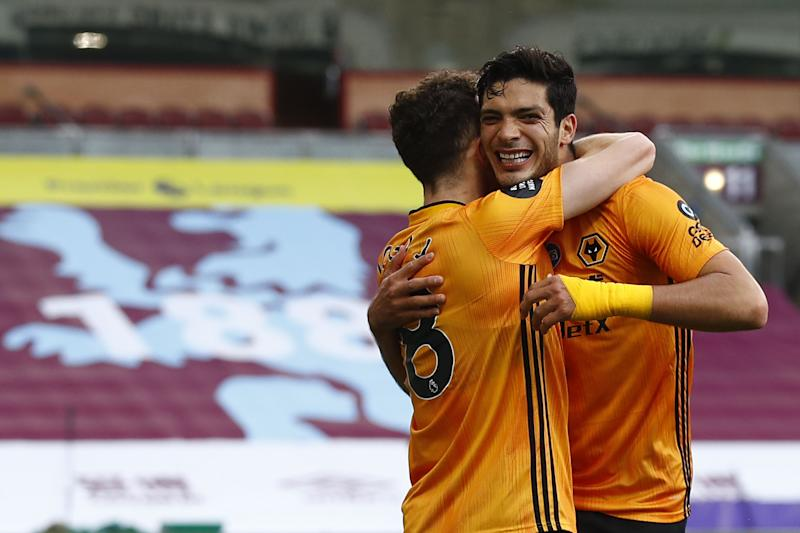 Wolverhampton Wanderers' Mexican striker Raul Jimenez (R) is congratulated by teammates after scoring a goal during the English Premier League football match between Burnley and Wolverhampton Wanderers at Turf Moor in Burnley, north-west England on July 15, 2020. (Photo by JASON CAIRNDUFF / POOL / AFP) / RESTRICTED TO EDITORIAL USE. No use with unauthorized audio, video, data, fixture lists, club/league logos or 'live' services. Online in-match use limited to 120 images. An additional 40 images may be used in extra time. No video emulation. Social media in-match use limited to 120 images. An additional 40 images may be used in extra time. No use in betting publications, games or single club/league/player publications. / (Photo by JASON CAIRNDUFF/POOL/AFP via Getty Images)