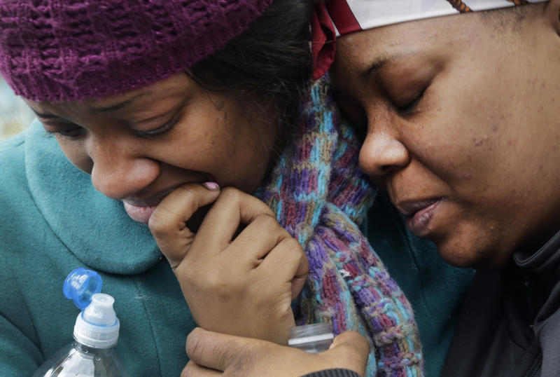 Alecia Thomas, left, is comforted by her friend, Shivon Dollar, after she lost her home following an explosion that leveled two apartment buildings in the East Harlem neighborhood of New York, Wednesday, March 12, 2014. Con Edison spokesman Bob McGee says a resident from a building adjacent to the two that collapsed reported that he smelled gas inside his apartment, but thought the odor could be coming from outside. (AP Photo/Mark Lennihan)