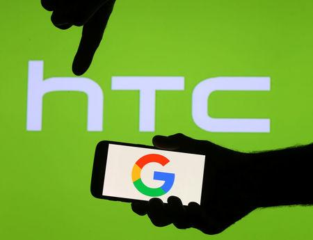 The Google logo is seen on a smartphone in front of a displayed HTC logo in this illustration