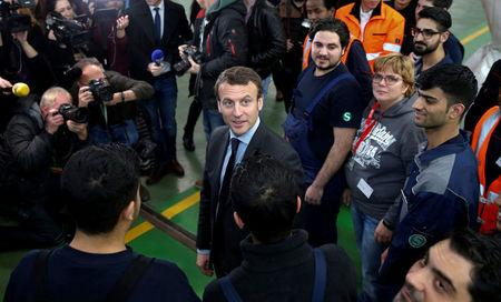 FILE PHOTO - Macron, candidate for the 2017 French presidential election, smiles during a visit to a qualification class for refugees of German railway operator Deutsche Bahn in Berlin
