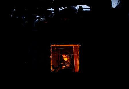 A Palestinian woman is seen from the window of her kitchen as she uses a candle light to prepare food during power cut in Beit Lahiya town in the northern Gaza Strip July 13, 2017.  REUTERS/Mohammed Salem