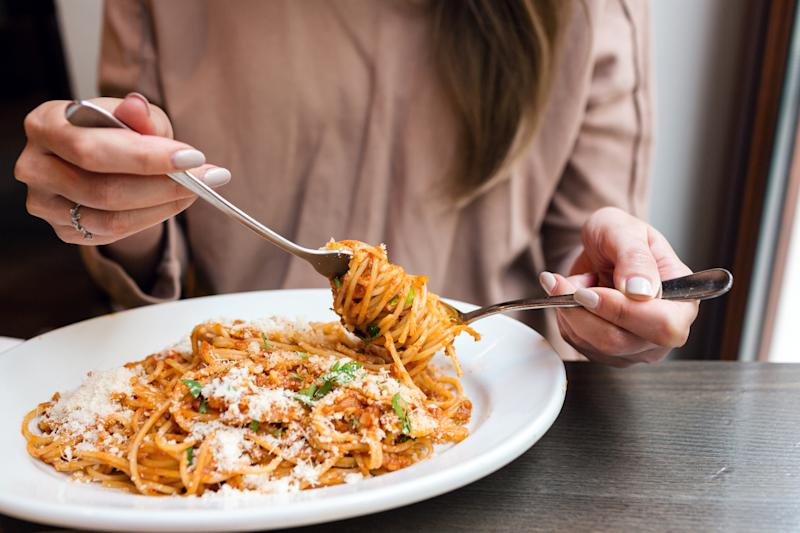 girl eats Italian pasta with tomato, meat. Close-up spaghetti Bolognese wind it around a fork with a spoon. Parmesan cheese.