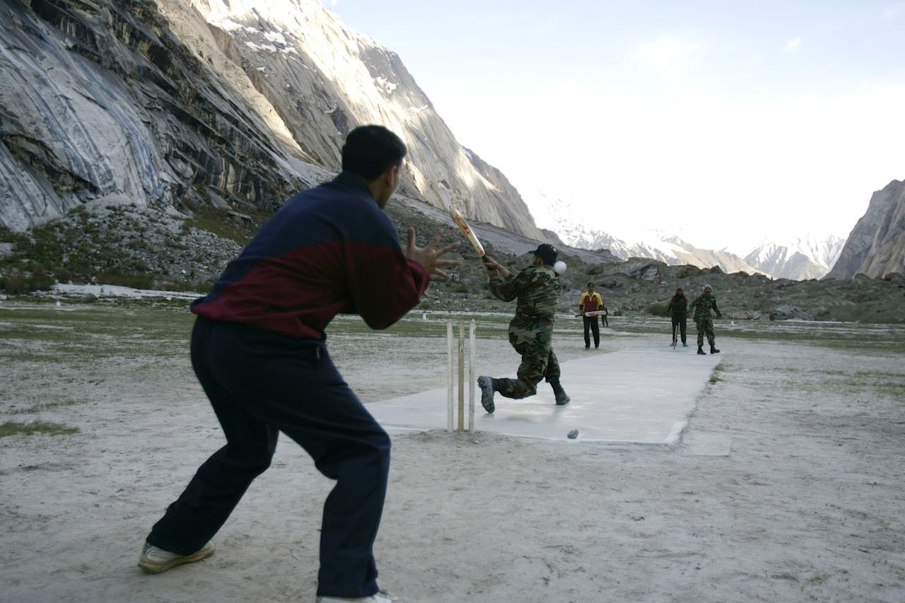 GYARI, PAKISTAN - JUNE 17:  (NEWSWEEK AND US NEWS AND WORLD REPORT OUT) Pakistani Army soldiers play an afternoon game of cricket at 13,800 feet June 17, 2005 in Gyari, Pakistan. Since 1982-84, the Pakistani Army has been facing off with the Indian Army in a 250-square-mile area of the Himalayan Mountains. Word of an Indian Army incursion first reached the Pakistani military from foreign mountaineers in 1982 when Indian Army troops were seen in the previously unoccupied Siachen Glacier area. Since Partition in 1947, the Siachen Glacier has been considered to be Pakistani territory. The two armies have been fighting costly artillery battles along Himalayan mountain peaks reaching up to 21,000 feet. Since November 2003, there has been a negotiated cease-fire in place and talks continue of a possible pull back from the disputed border area. The two armies suffer a greater number of casualties from frostbite, pulmonary and cerebral edema and high altitude sickness than they do from shelling or bullets. Pakistan keeps an estimated 3000 soldiers in the mountainous area at any one time. India spends an estimated $1 million USD per day to maintain its troops. Figures for Pakistan are similar for strength and outlays. The Siachen Glacier is part of the Karakoram mountain range between Pakistan, China and India.  (Photo by Robert Nickelsberg/Getty Images)