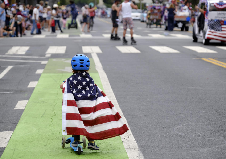 Two and a half year old Zacky Kaplan rides his scooter while draped in the American flag as he makes his way along the parade route during the Santa Monica Fourth of July Parade on July 4, 2019 in Santa Monica, Calif. (Photo: Richard Vogel/AP)