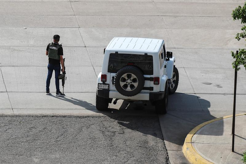"""A cartel gunmen wearing a flack jacket stands next to his vehicle during clashes with federal forces following the detention of Ovidio Guzman, son of drug kingpin Joaquin """"El Chapo"""" Guzman, in Culiacan, Sinaloa state, Mexico October 17, 2019. REUTERS/Jesus Bustamante"""