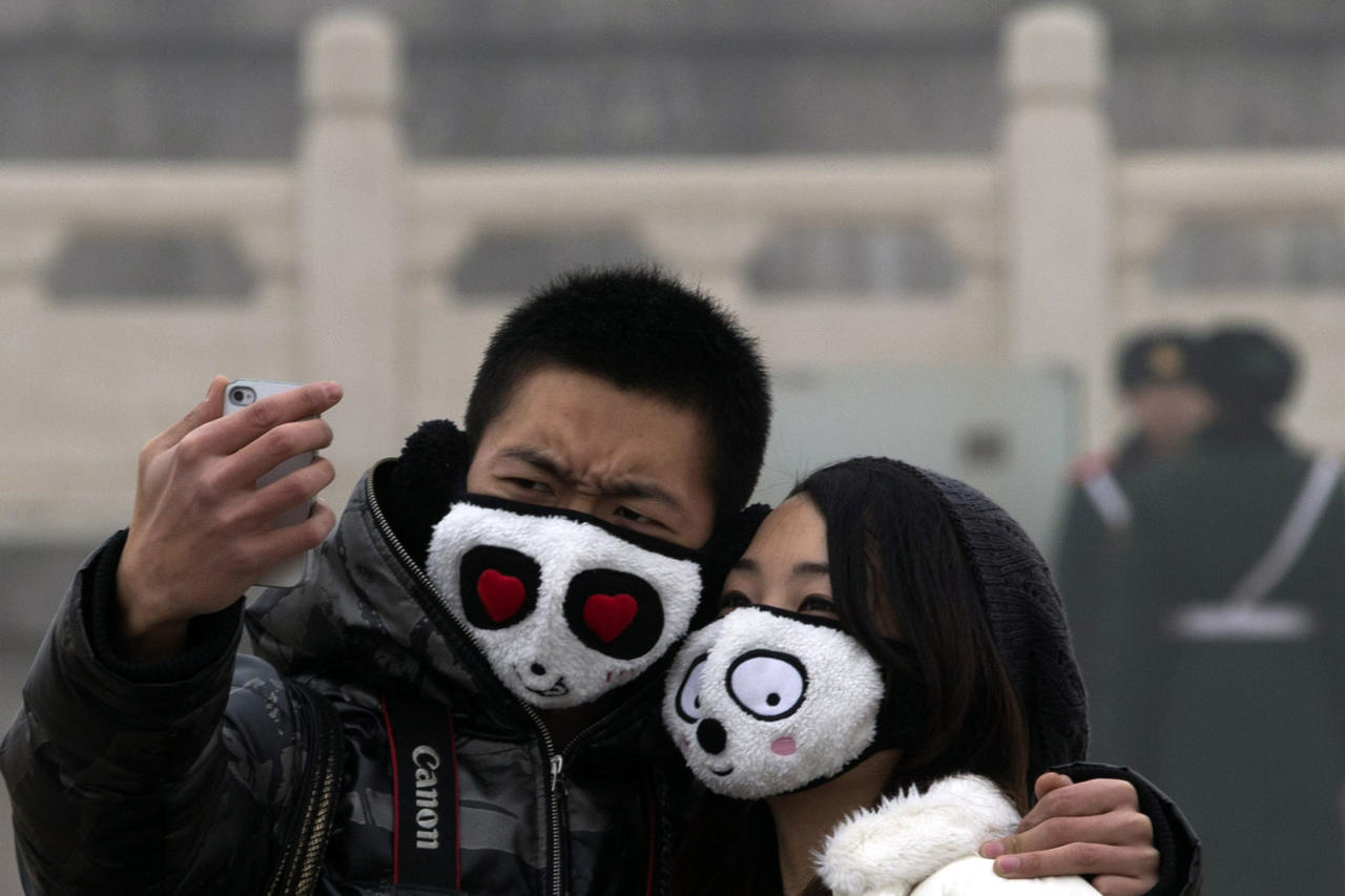 A couple wearing protective masks poses for a self portrait in thick haze on Tiananmen Square in Beijing Tuesday, Jan. 29, 2013. Extremely high pollution levels shrouded eastern China for the second time in about two weeks Tuesday, forcing airlines in Beijing and elsewhere to cancel flights because of poor visibility and prompting government warnings for residents to stay indoors. (AP Photo/Ng Han Guan)