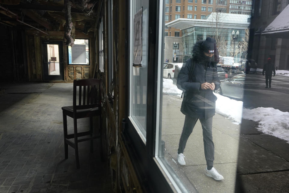 FILE - In this Feb. 10, 2021, file photo, a passerby walks past an empty building that was formerly a restaurant in Boston. Massive fraud in the nation's unemployment system is raising alarms even as President Joe Biden and Congress prepare to pour hundreds of billions more into expanded benefits for those left jobless by the coronavirus pandemic. (AP Photo/Steven Senne, File)