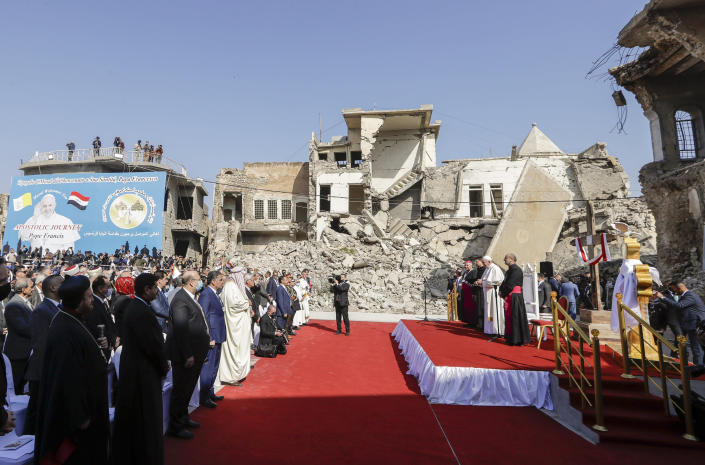 Pope Francis, surrounded by shells of destroyed churches, attends a prayer for the victims of war at Hosh al-Bieaa Church Square, in Mosul, Iraq, once the de-facto capital of IS, Sunday, March 7, 2021. The long 2014-2017 war to drive IS out left ransacked homes and charred or pulverized buildings around the north of Iraq, all sites Francis visited on Sunday. (AP Photo/Andrew Medichini)