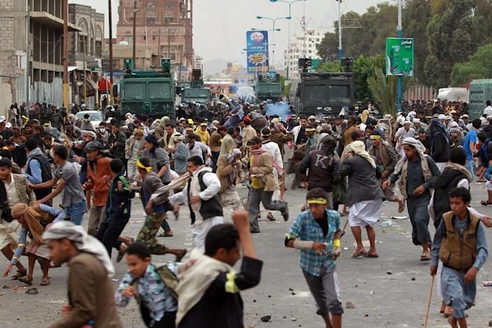 Yemeni protesters run to take cover from tear gas fired by riot police during clashes with Shiite Huthi rebels after they blocked the road to Sanaa airport on September 7, 2014, in Sanaa (AFP Photo/Mohammed Huwais)