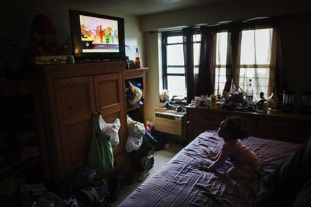 A young child watches television in an NYCHA apartment after receiving electricity just minutes before for the first time following Hurricane Sandy in the Brooklyn borough neighborhood of Coney Island in New York
