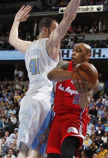 Denver Nuggets center Kosta Koufos, left, blocks Los Angeles Clippers forward Caron Butler who drives the lane for a shot in the first quarter of an NBA basketball game in Denver, Thursday, March 7, 2013. (AP Photo/David Zalubowski)