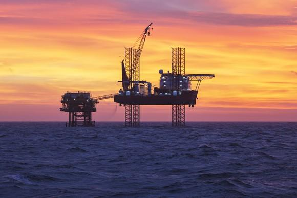 An offshore oil rig in silhouette in open water at sunset