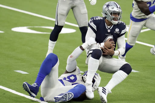 Dallas Cowboys quarterback Dak Prescott, right, is tackled by Los Angeles Rams defensive end Michael Brockers during the first half of an NFL football game Sunday, Sept. 13, 2020, in Inglewood, Calif. (AP Photo/Jae C. Hong )
