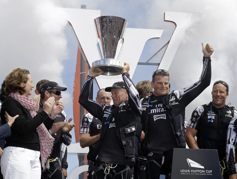 Emirates Team New Zealand managing director Grant Dalton hoists the Louis Vuitton Cup as skipper Dean Barker gives a thumbs-up during an awards ceremony following the eighth race of their America's Cup challenger series final sailing event against Luna Rossa Challenge, of Italy, Sunday, Aug. 25, 2013, in San Francisco. Emirates Team New Zealand won the race and series and will compete against Oracle Team USA next month. Grinder Chris McAsey, right, looks on. (AP Photo/Eric Risberg)