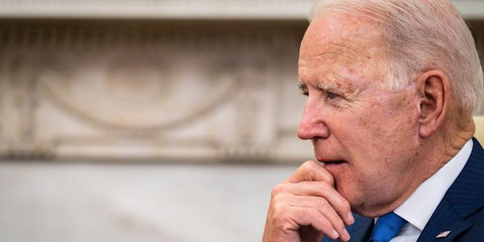 joe biden holds his hand to his chin as he speaks
