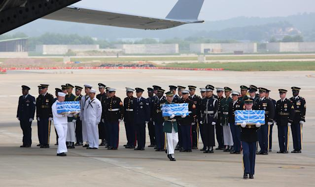 U.N. honor guards carry small boxes containing remains believed to be from American servicemen killed during the 1950-53 Korean War after they arrived from North Korea, at Osan Air Base in Pyeongtaek, South Korea, Friday, July 27, 2018. Ahn Young-joon/Pool via Reuters
