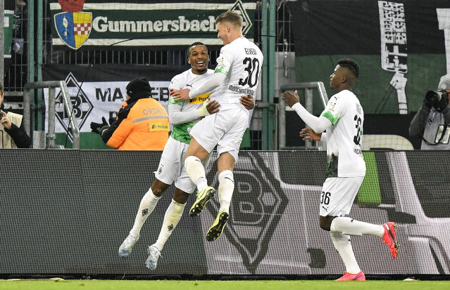 Moenchengladbach's Alassane Plea, left, is celebrated after he scored his second goal during the German Bundesliga soccer match between Borussia Moenchengladbach and FSV Mainz 05 in Moenchengladbach, Germany, Saturday, Jan. 25, 2020. (AP Photo/Martin Meissner)