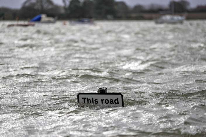 A street sign is seen under flood water in Bosham caused by the high tide, in England, Monday, Feb. 10, 2020. Storm Ciara battered the U.K. and northern Europe with hurricane-force winds and heavy rains Sunday, halting flights and trains and producing heaving seas that closed down ports. Propelled by the fierce winds, a British Airways plane was thought to have made the fastest New York-to-London flight by a conventional airliner. (Steve Parsons/PA via AP)