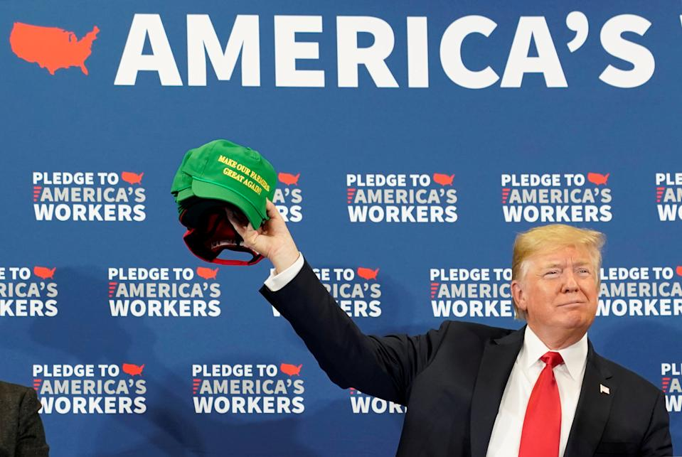 """REFILE CORRECTING WORDING ON HAT U.S. President Donald Trump holds up a """"Make Our Farmers Great Again"""" cap during a roundtable discussion on workforce development at Northeast Iowa Community College in Peosta, Iowa, U.S., July 26, 2018. REUTERS/Joshua Roberts      TPX IMAGES OF THE DAY"""