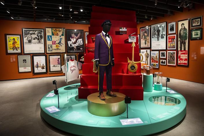 A platform houses a mannequin wearing a purple suit, a red staircase with a Prince guitar on it, a jersey and a statuette