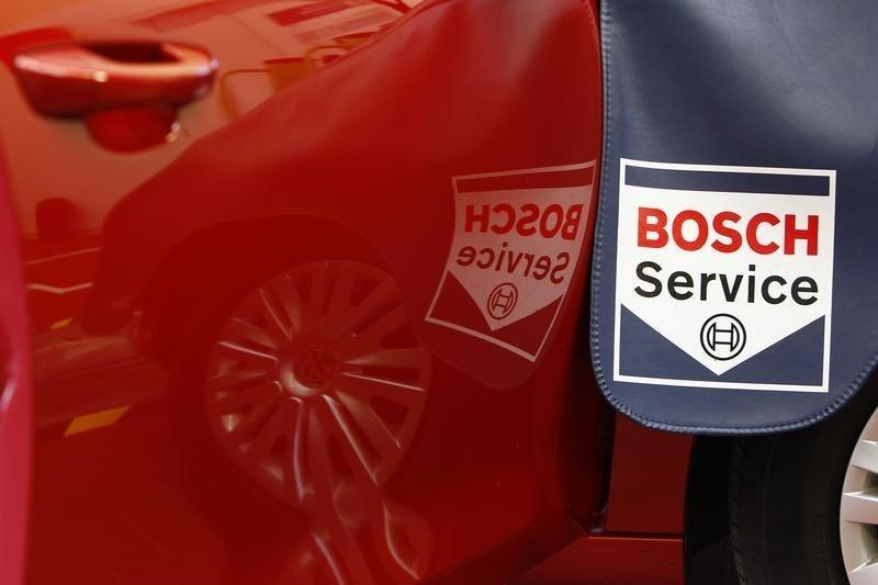 Service sign is reflected in car door while product expert for diagnostics equipment of German auto parts supplier Robert Bosch analyses a car in garage in Plochingen