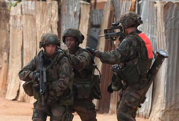 French soldiers cover each other as they secure an area of the Miskine neighborhood of Bangui, Central African Republic, Thursday, Dec. 26, 2013. The spokesman for an African Union peacekeeping force says six Chadian peacekeepers were killed and 15 were wounded, after being attacked Wednesday.(AP Photo/Rebecca Blackwell)