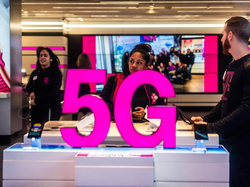 Customers at a T-Mobile store, with 5G signage in February 2020.