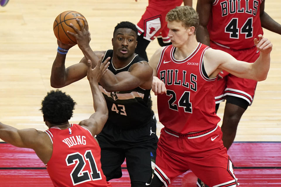 Milwaukee Bucks forward Thanasis Antetokounmpo, center, looks to pass as Chicago Bulls defenders Thaddeus Young, left, and Lauri Markkanen, right, guard during the first half of an NBA basketball game in Chicago, Sunday, May 16, 2021. (AP Photo/Nam Y. Huh)