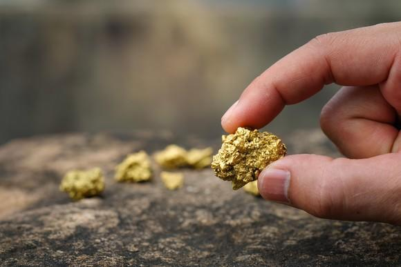 A closeup of a thumb and forefinger holding a gold nugget over a rocky surface.